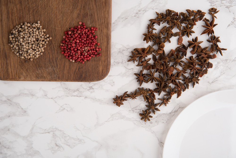 Close up portrait of anise seeds, spicy red and white peppers on wooden cutting board on white marble background