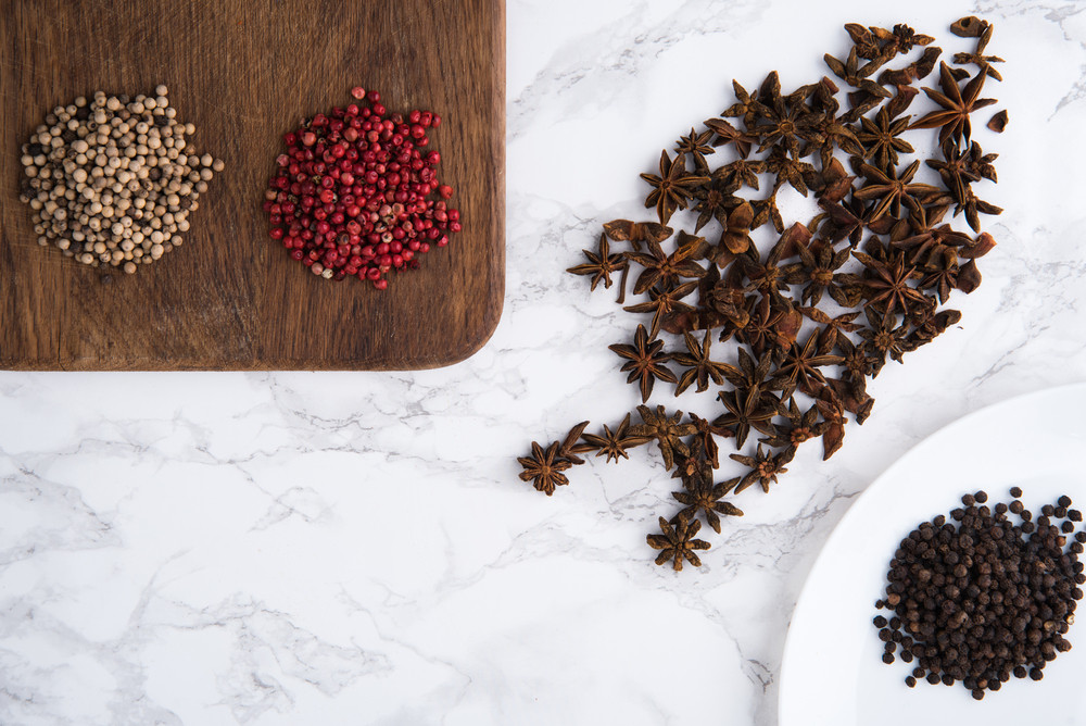 Close up portrait of anise seeds, spicy red, white and black peppers on wooden cutting board on white marble background