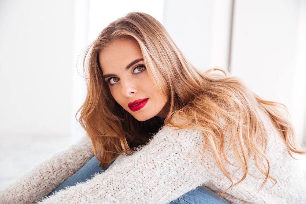 Close up portrait of beautiful blonde woman wearing sweater and red lipstick looking at camera