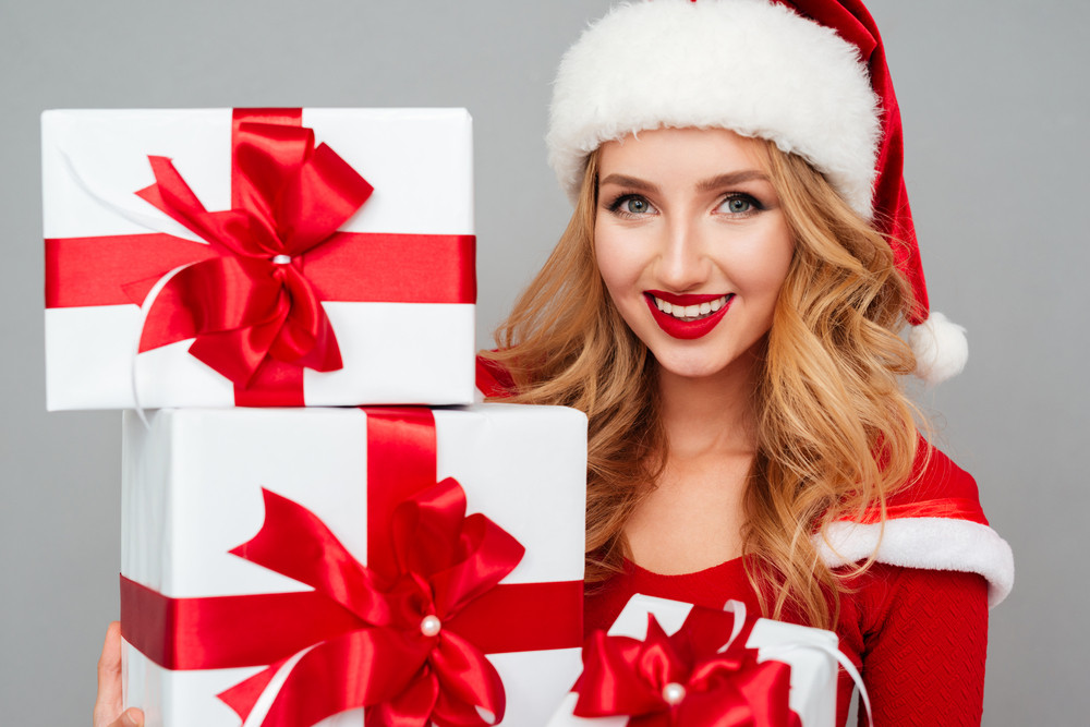 Close up portrait of beautiful smiling blonde woman in red dress holding stack of gift boxes isolated on the gray background