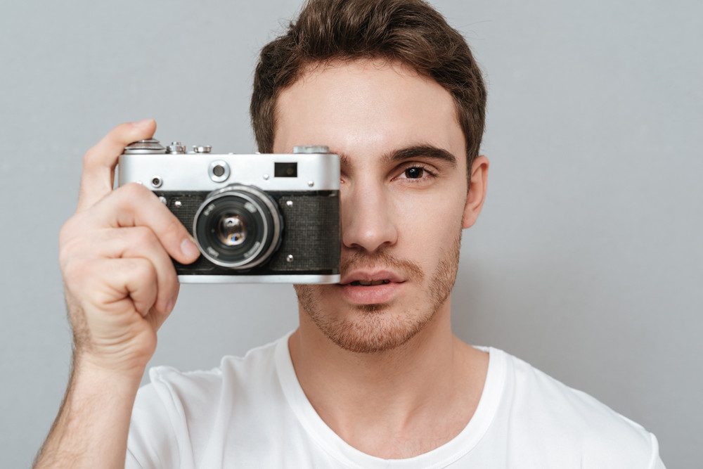 Close up portrait of Man making photo on retro camera. Isolated gray background