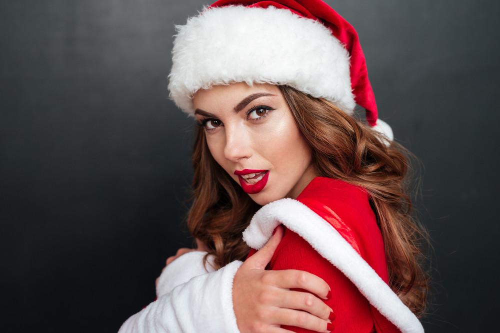 Close-up portrait of santa's helper over black background