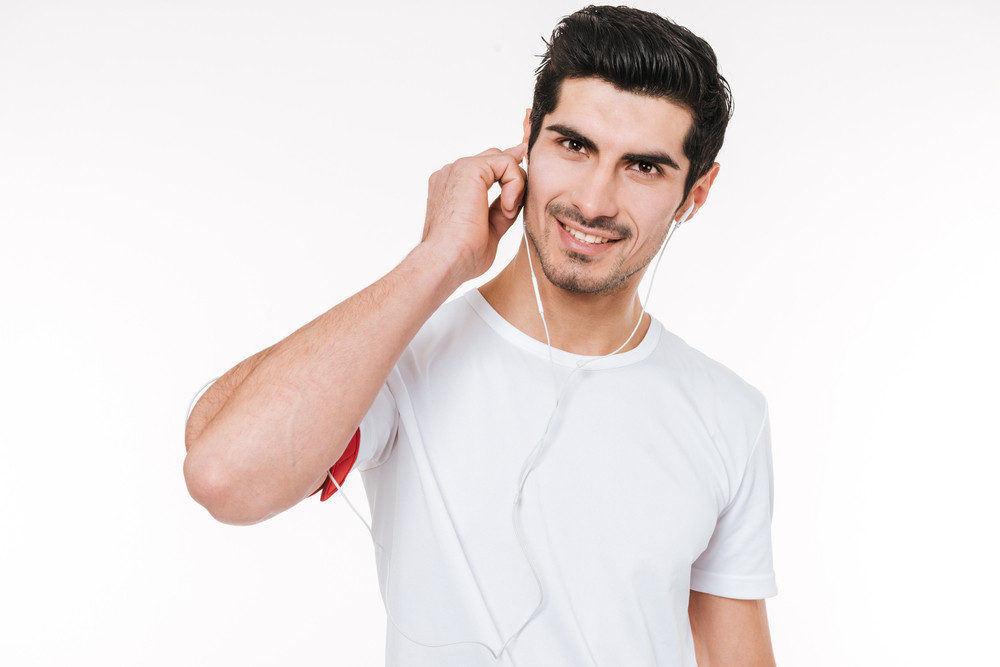 Close up portrait of smiling young male athlete listening to music with earphones over white background
