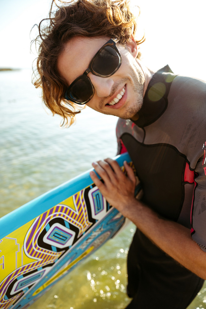 Close up portraut of a young curly man in eyeglasses and swimsuit holding surf board at the beach