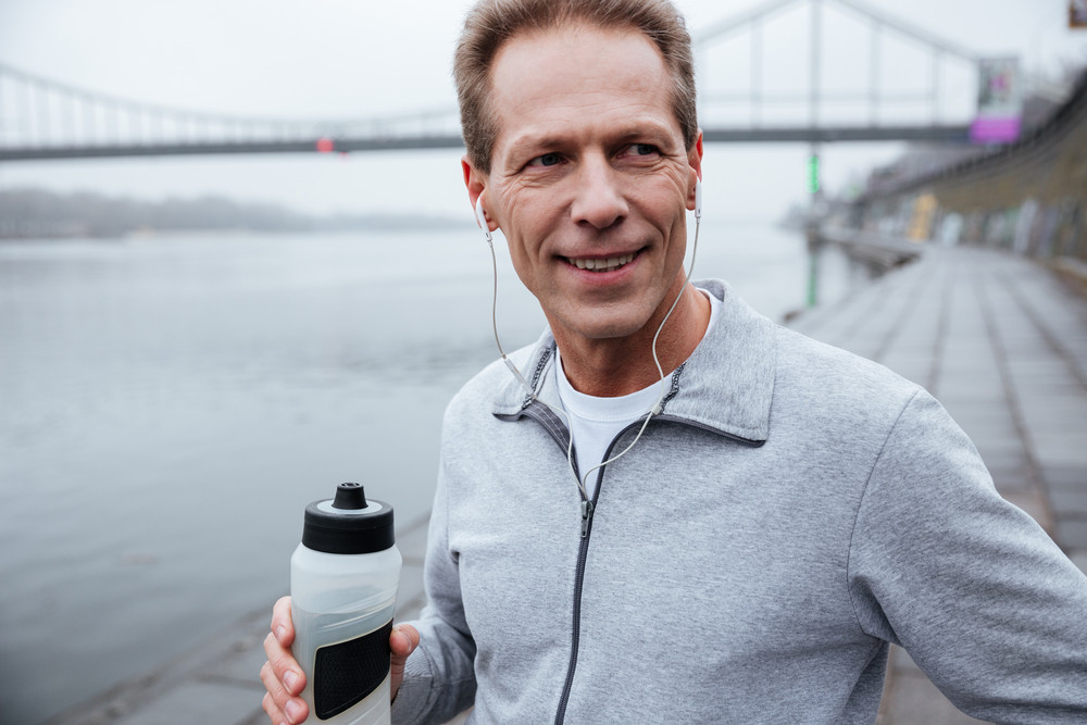 Close up runner in gray sportswear standing near the river with bottle of water in hand and looking away
