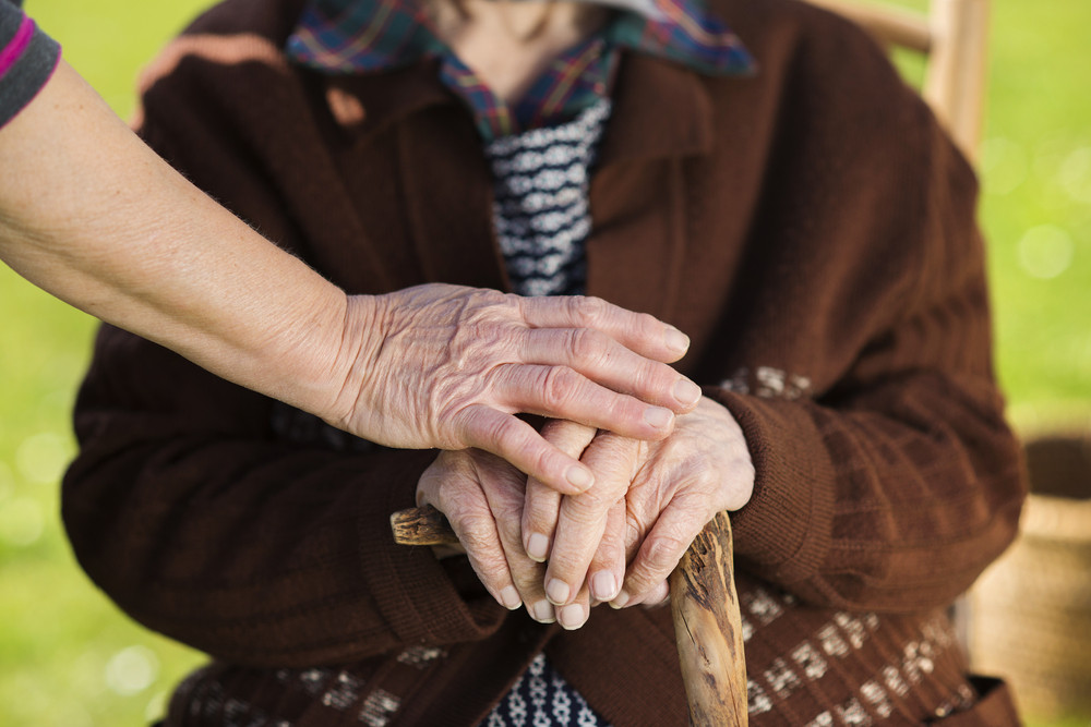 Closeup of caring woman holding female senior's hands