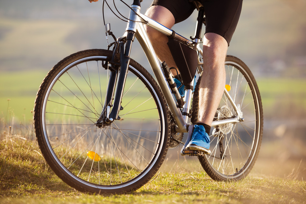Closeup of cyclist man legs riding mountain bike on outdoor trail in nature