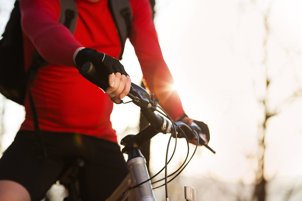 Closeup of cyclist man riding mountain bike on outdoor trail in autumn forest