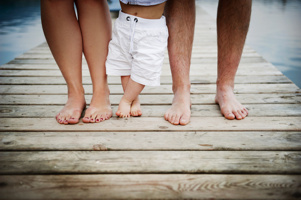 Closeup of feet of family with little baby boy walking on pier
