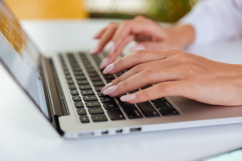 Closeup of hands of businesswoman working and typing on laptop