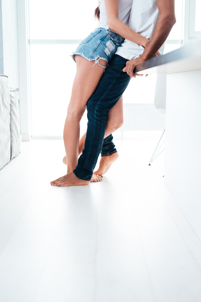 Closeup of legs of couple hugging and leaning on the table in the kitchen