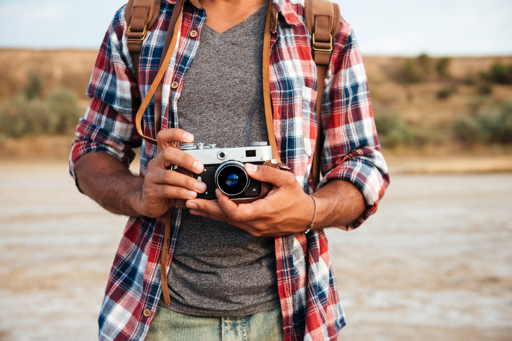 Closeup of man in plaid shirt standing and holding old vintage photo camera