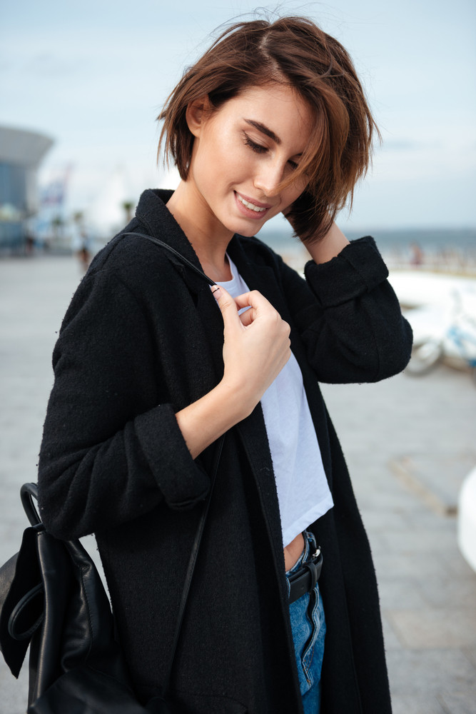 Closeup of smiling attractive young woman with backpack standing outdoors