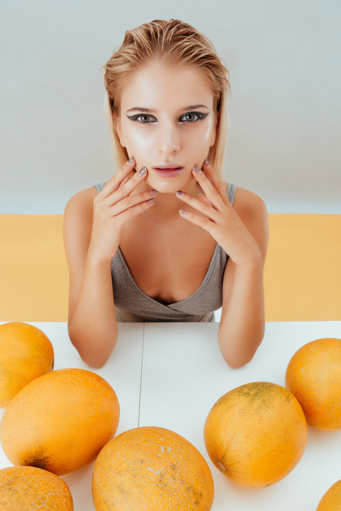 Closeup of stylish young woman with yellow melons sitting at the table over grey and yellow background