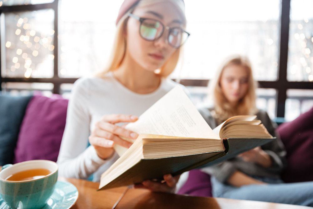 Closeup of two attractive young women sitting and reading books in cafe