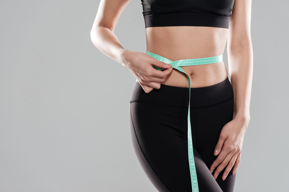 Closeup of woman athlete standing and using measuring tape on her waist over gray background