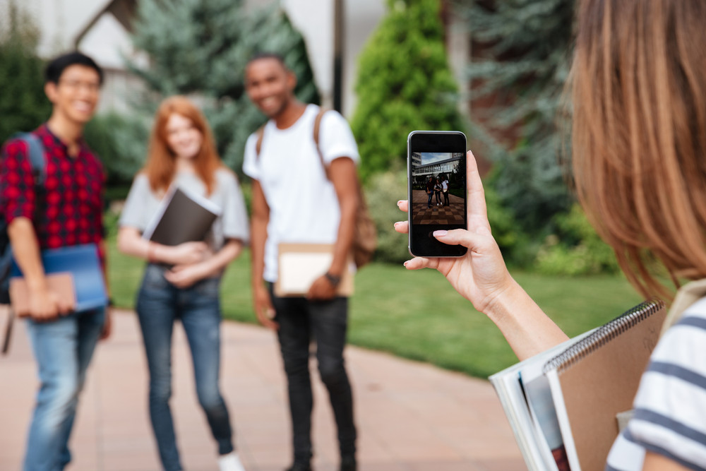 Closeup of woman student taking pictures of her friends with mobile phone outdoors