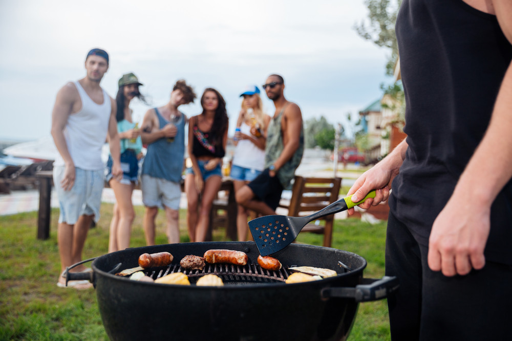 Closeup of young man standing and cooking sauseges on barbeque party