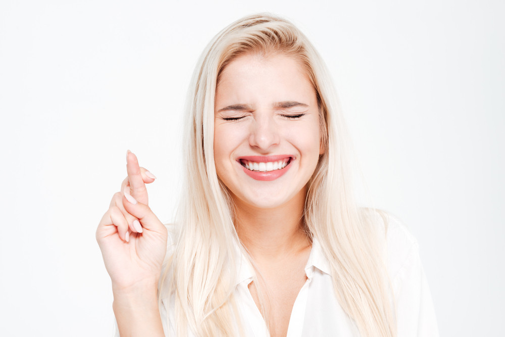 Closeup portrait of a smiling woman with fingers crossed gesture and eyes closed isolated on a white background