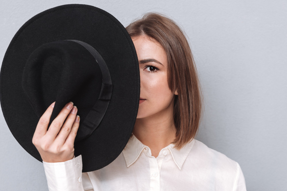 Closeup portrait of a woman covering half of her face with hat and looking at camera