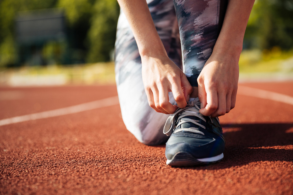 Closeup portrait of a young woman tying sneakers at the stadium track