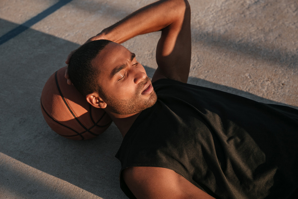 Closr up portrait of a tired afro american sports man resting on a basketball at the playground