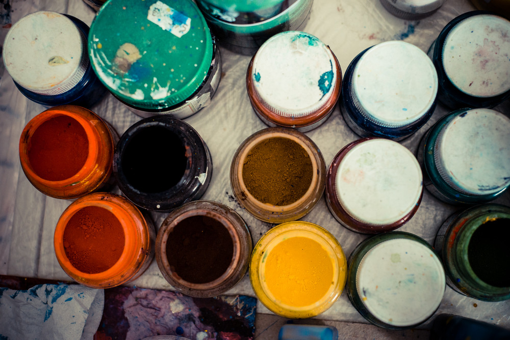 colored jars of powder paint in a painter studio
