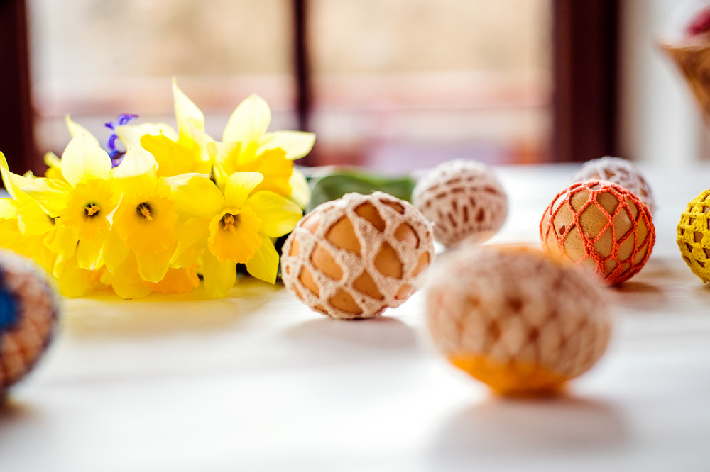 Colorful crocheted Easter eggs and fresh daffodil bouquet laid on white wooden table