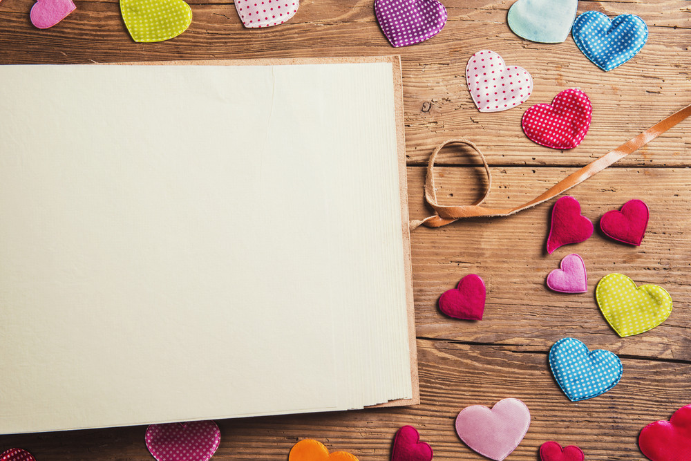 Composition with fabric hearts and empty piece of paper. Studio shot on wooden background.