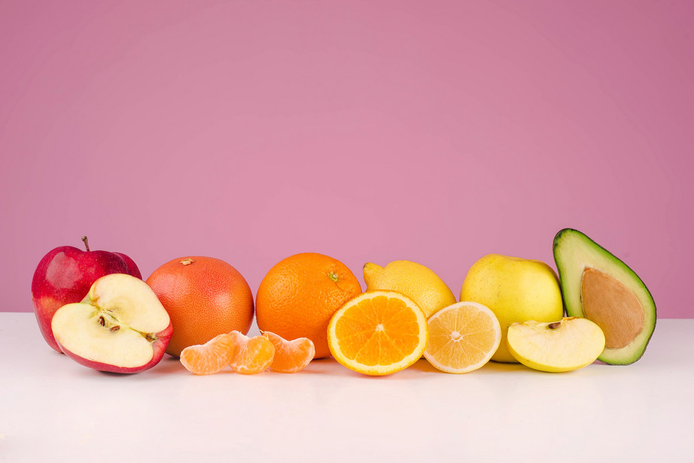 Composition with fresh sliced peeed fruits apple, grapefruit, orange, lemon, apple, avocado on a table isolated on a pink background
