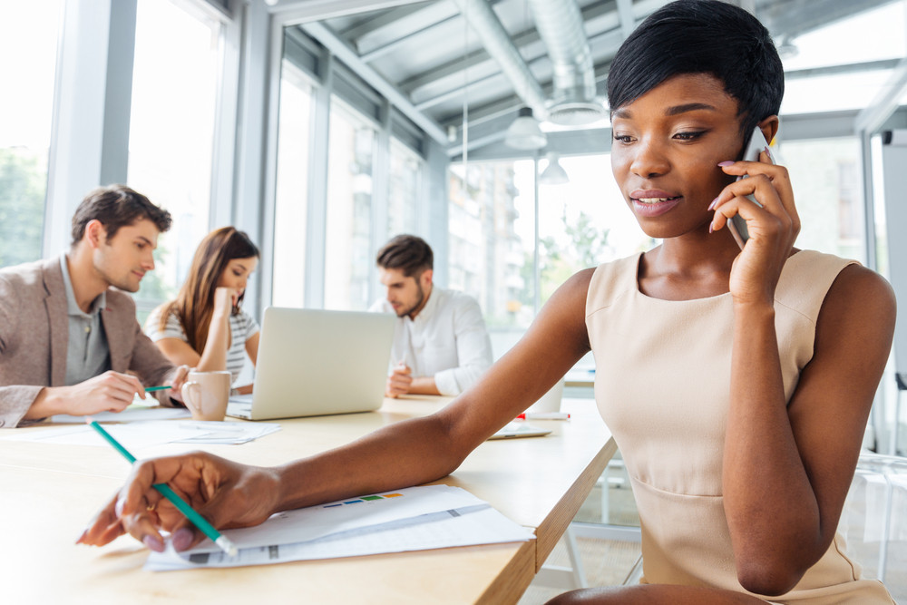 Concentrated african american young businesswoman talking on cell phone in office