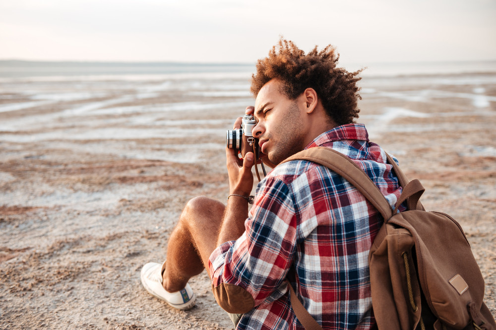 Concentrated african american young man with backpack sitting and taking pistures outdoors