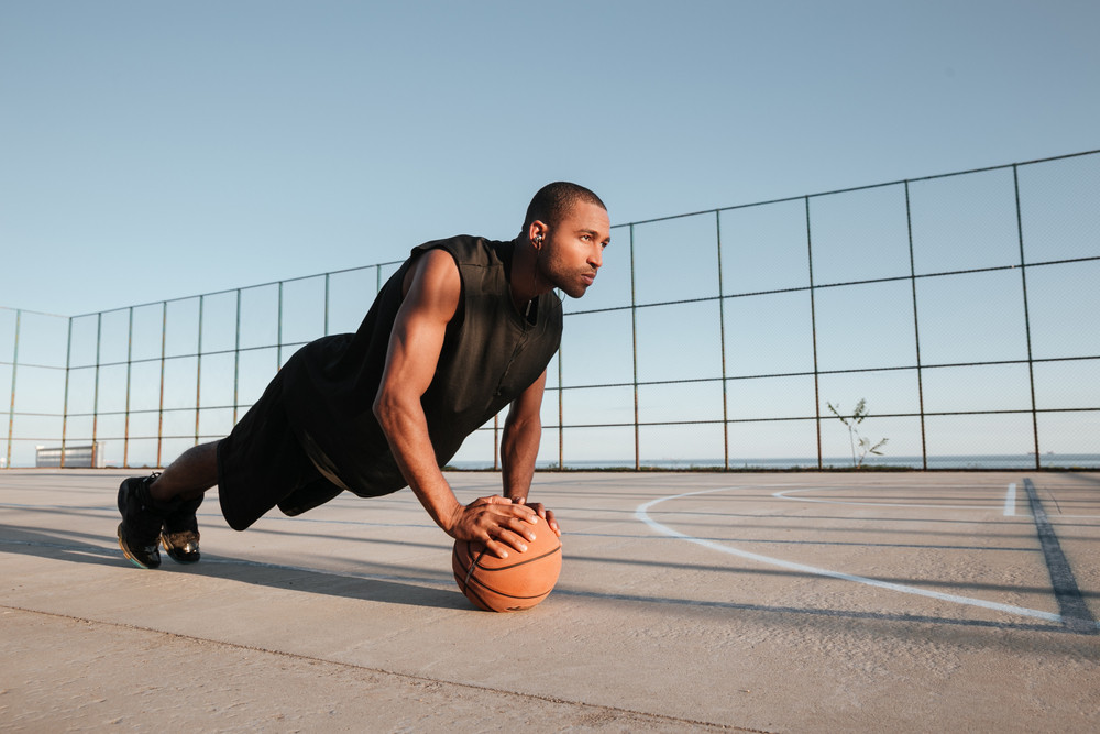 Concentrated african sports man doing plank exercise with ball at the playground