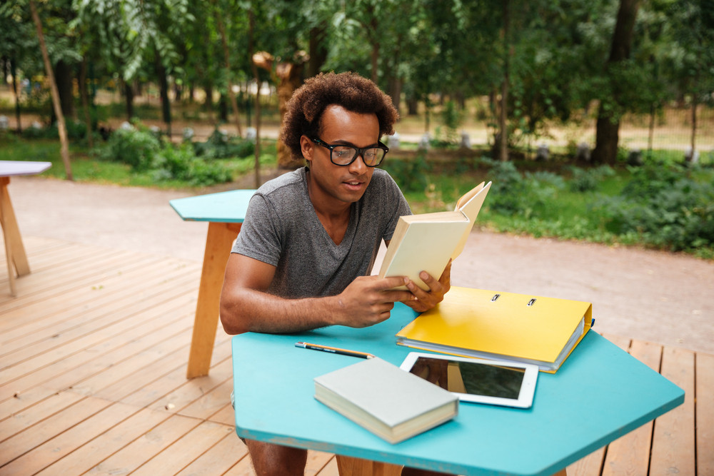 Concentrated african young man sitting and reading book outdoors