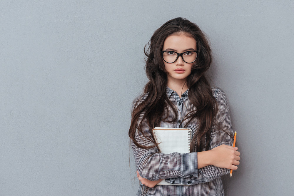 Concentrated Asian woman in glasses holding notebook and looking at camera. Isolated gray background