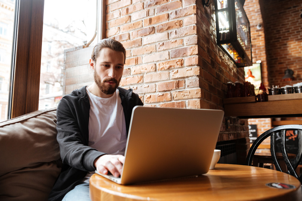 Concentrated Bearded man sitting by the table and using laptop in cafe