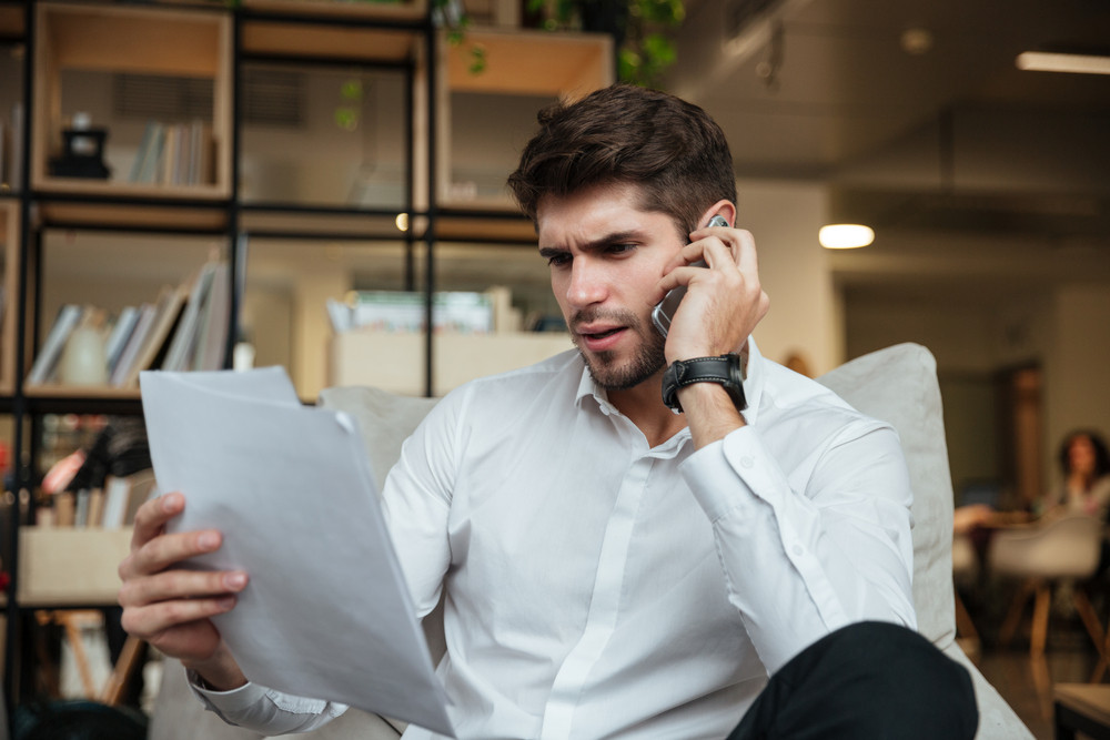 Concentrated businessman dressed in white shirt sitting in cafe and talking by phone while looking at documents.