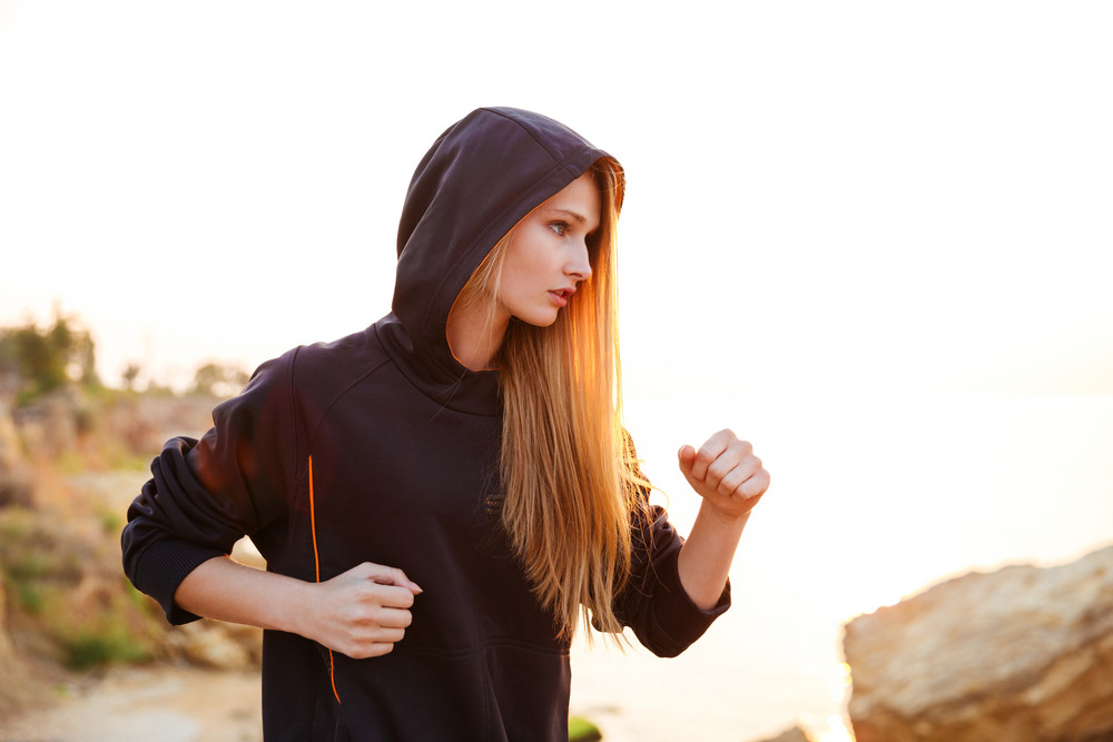 Concentrated healthy young woman in hoodie running along beach