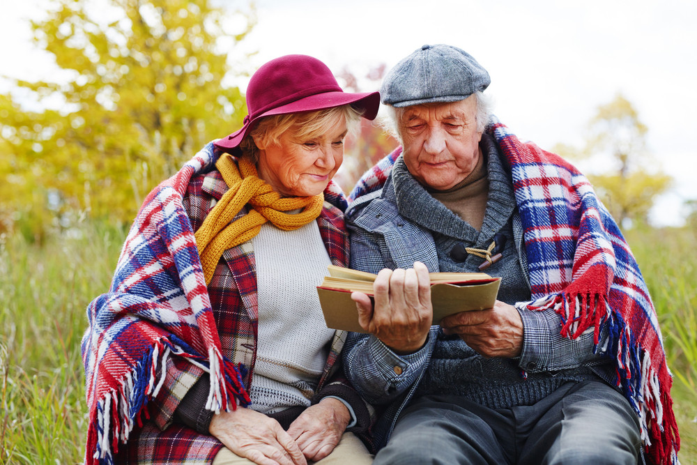 Concentrated senior couple reading interesting book outdoors