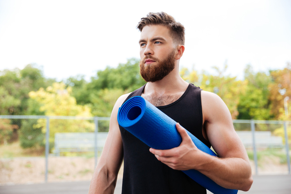 Concentrated serious male yoga instructor holding mat while standing outdoors
