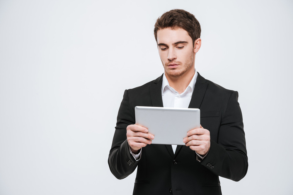 Concentrated young businessman standing and using tabet over white background