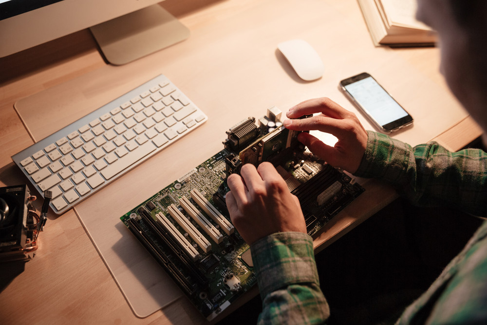 Concentrated young man sitting and repairing motherboard in the dark room