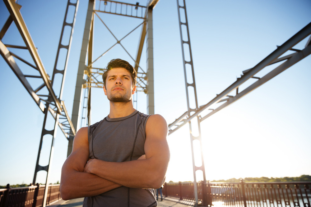 Concentrated young sports man resting after running while standing on the bridge with hands crossed