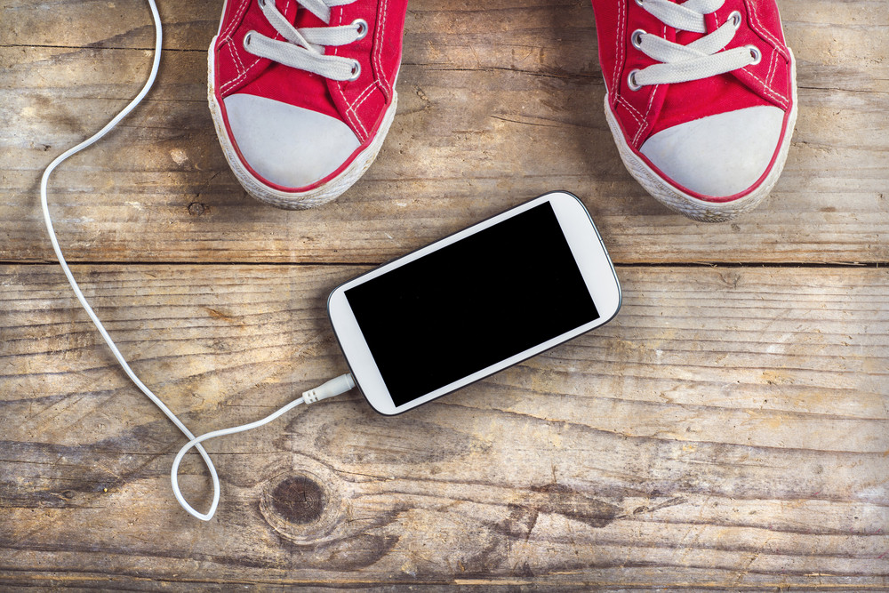 Concept with red sneakers and smartphone laid on wooden floor background.