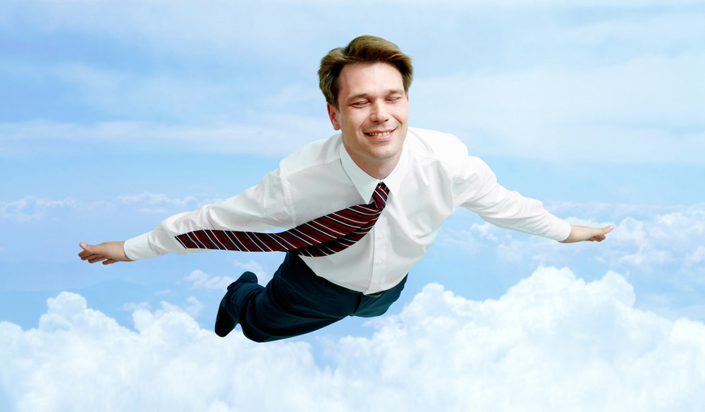 Conceptual image of smiling businessman enjoying flying in the clouds