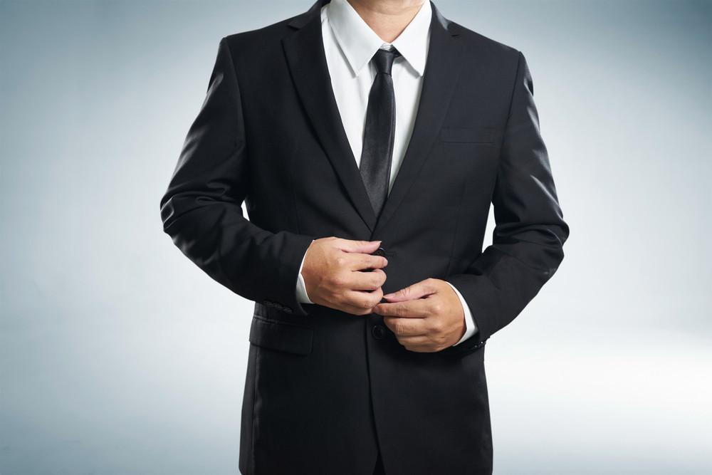 Confidence businessman in black suit , close up .