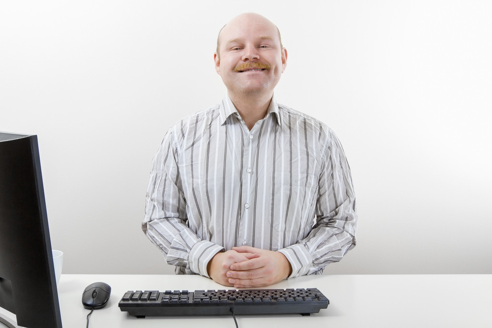 Confident Businessman Smiling At Computer Desk