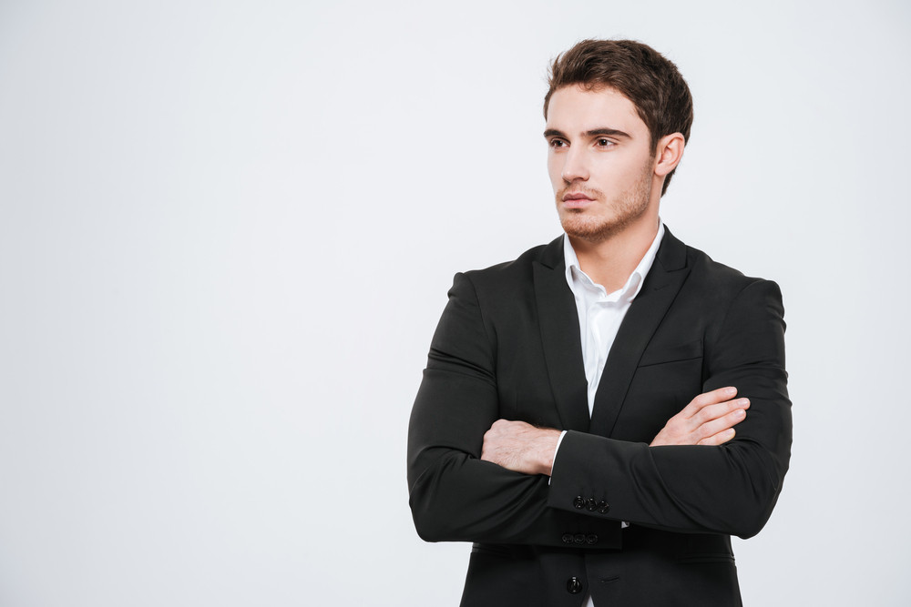 Confident businessman standing with arms folded and looking away over white background