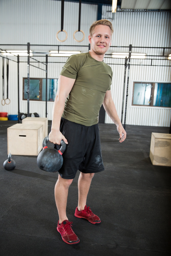 Confident Male Athlete Lifting Kettlebell In Health Club