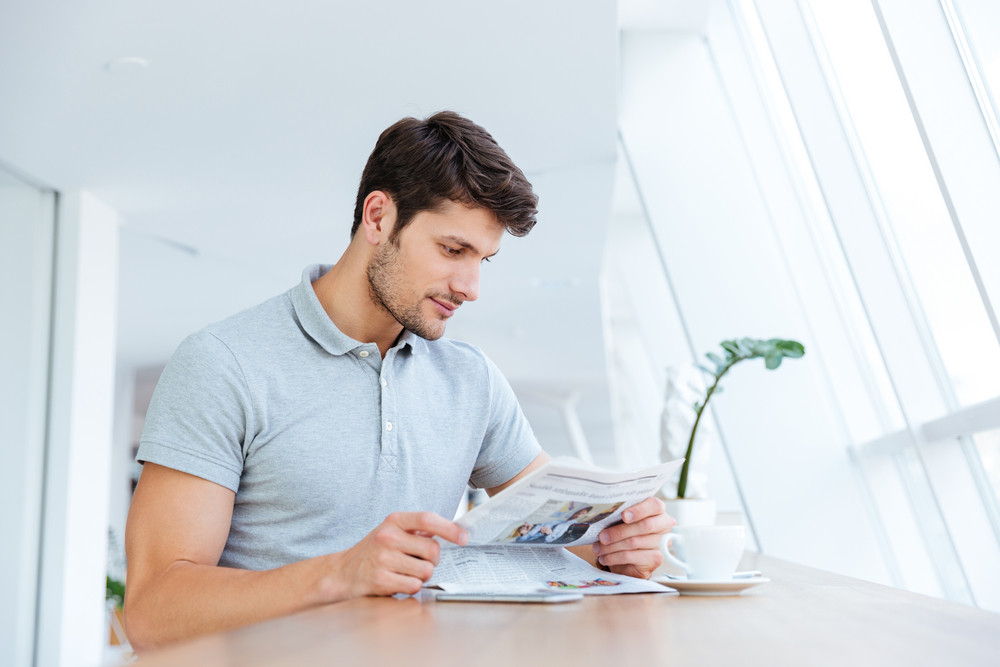Confident young businessman reading newspaper and drinking coffee indoors